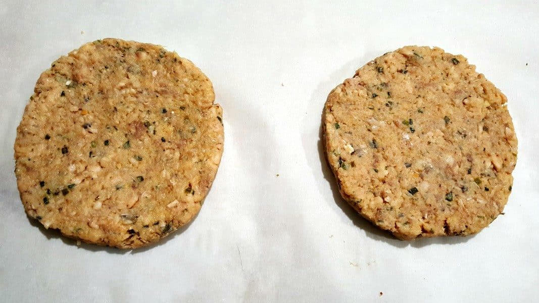 two salmon burger patties on parchment paper