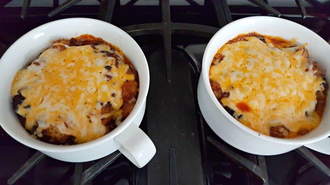 baked taco tater tot casserole topped with melted cheese in two baking dishes