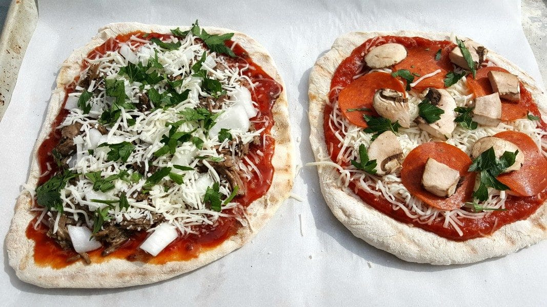 two uncooked pizzas with toppings added ready to grill