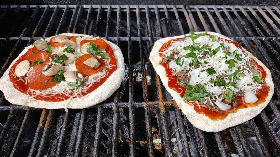 two pizzas with toppings cooking on a grill