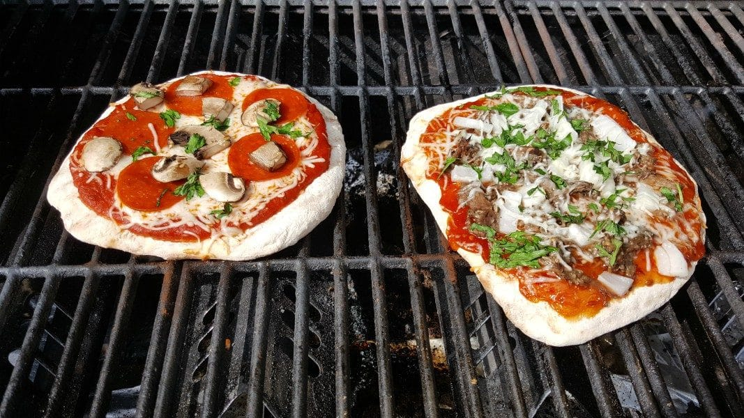 two pizzas cooking on a grill ready to be taken off