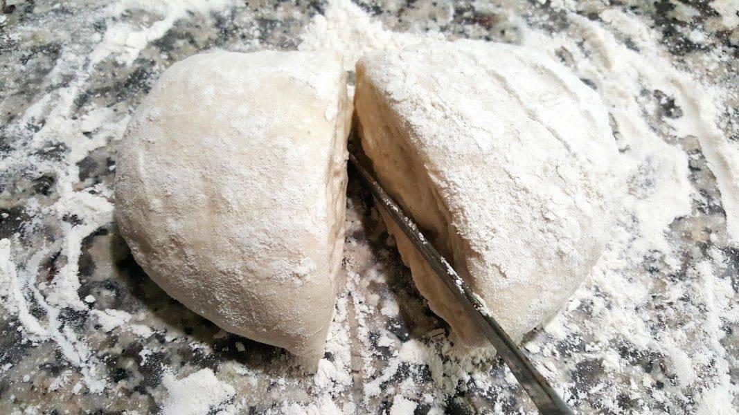 cutting pizza dough in half