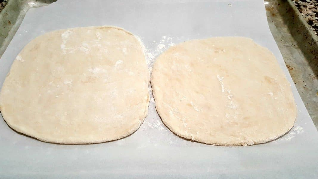 to circles of pizza dough on a baking sheet
