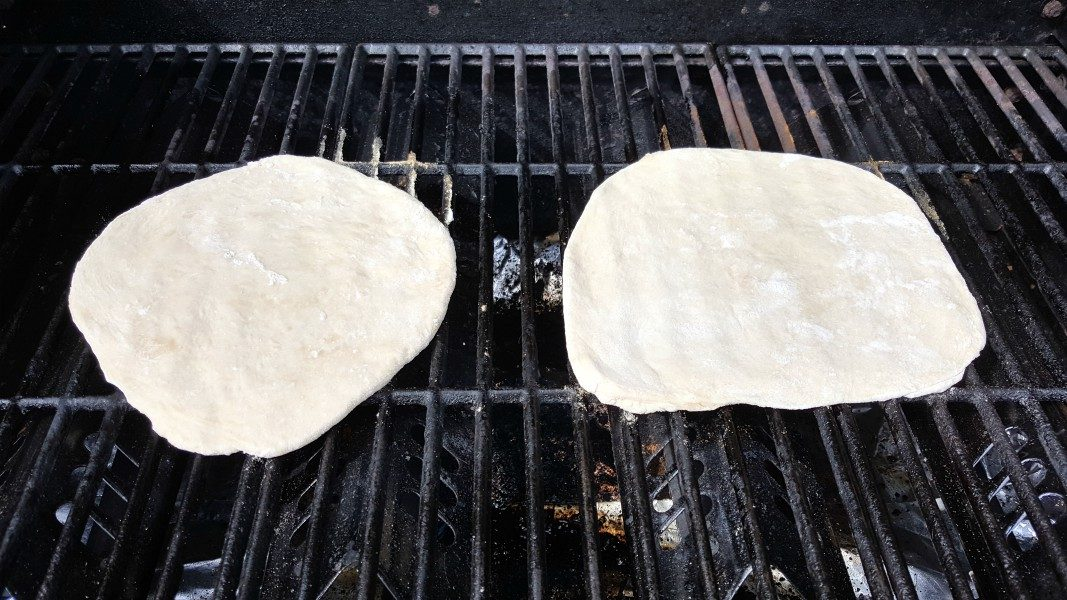 two circles of pizza dough on a grill