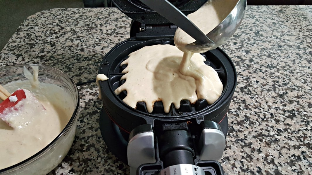 pouring waffle batter into the first side of the waffle iron