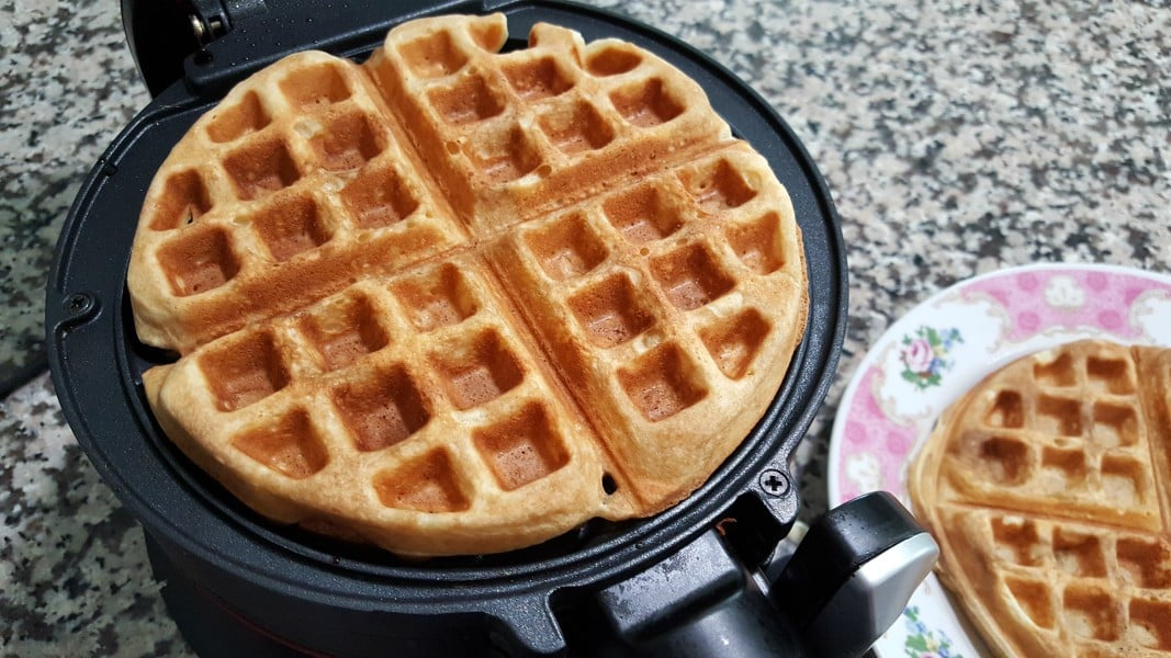 cooked waffle in the iron and a plate with second waffle