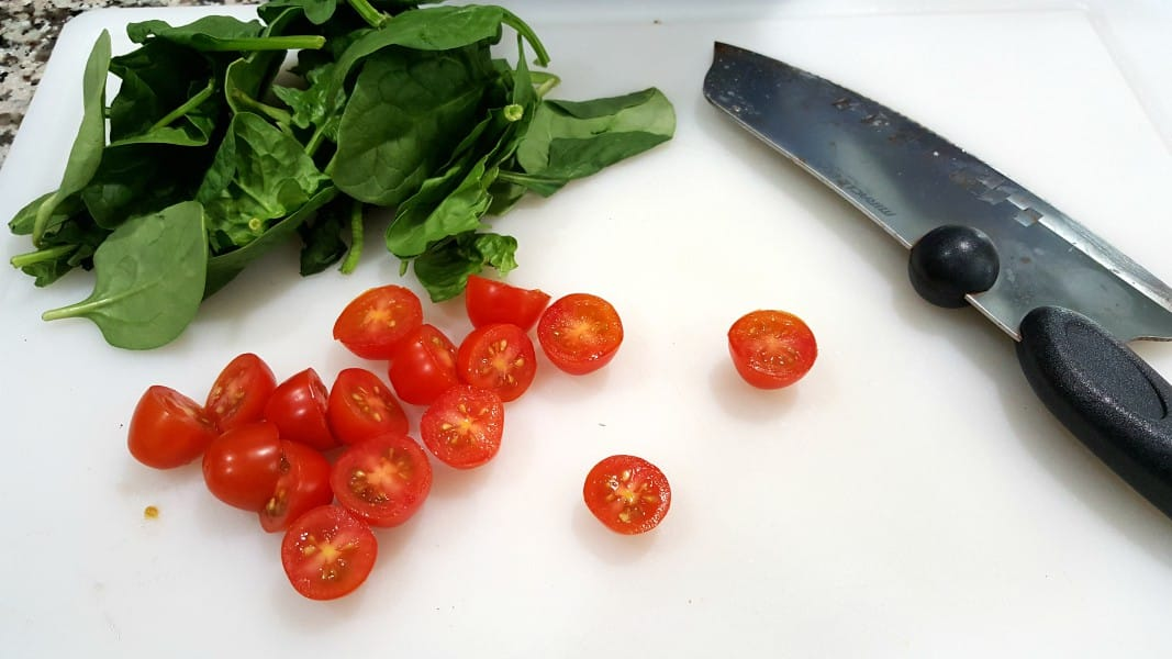 Cherry tomatoes cut in half with a knife and pile of baby spinach