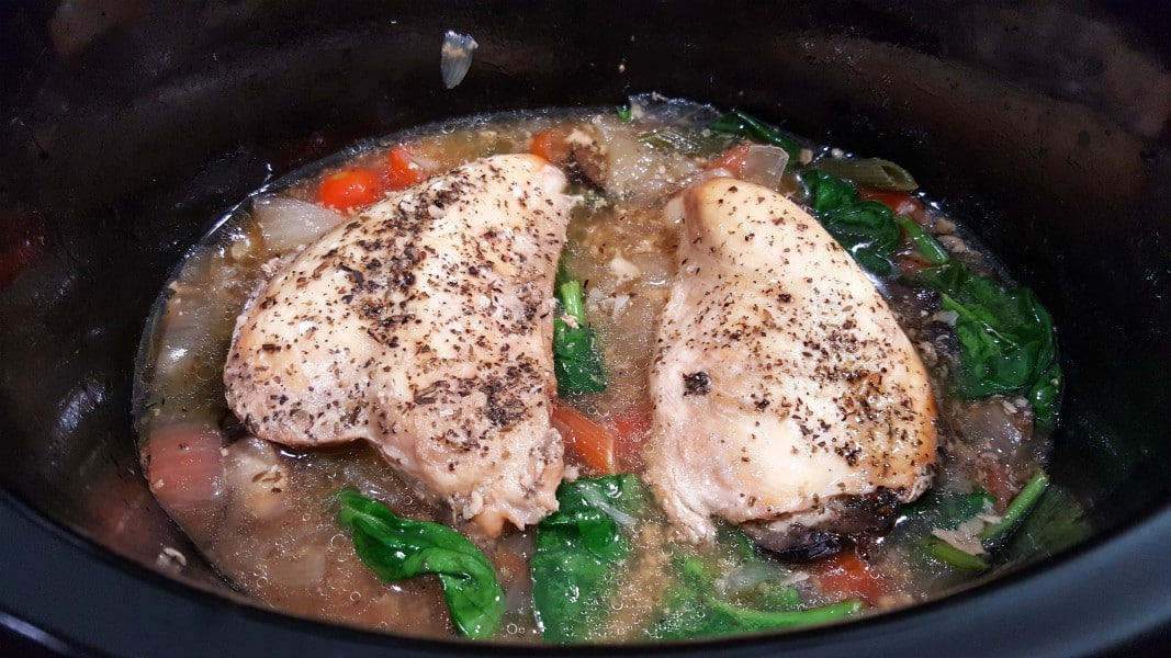 Tuscan Chicken and ingredients in a crockpot slow cooker.