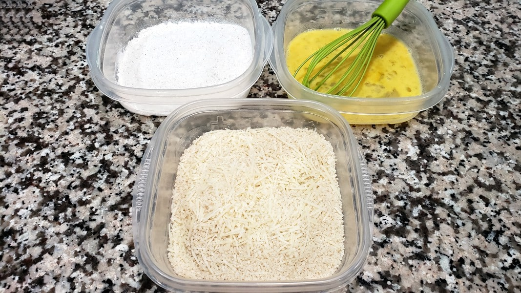 three dishes, first has flour and seasoning mixture, second is egg and water mixture, third is panko and parmesan mixture
