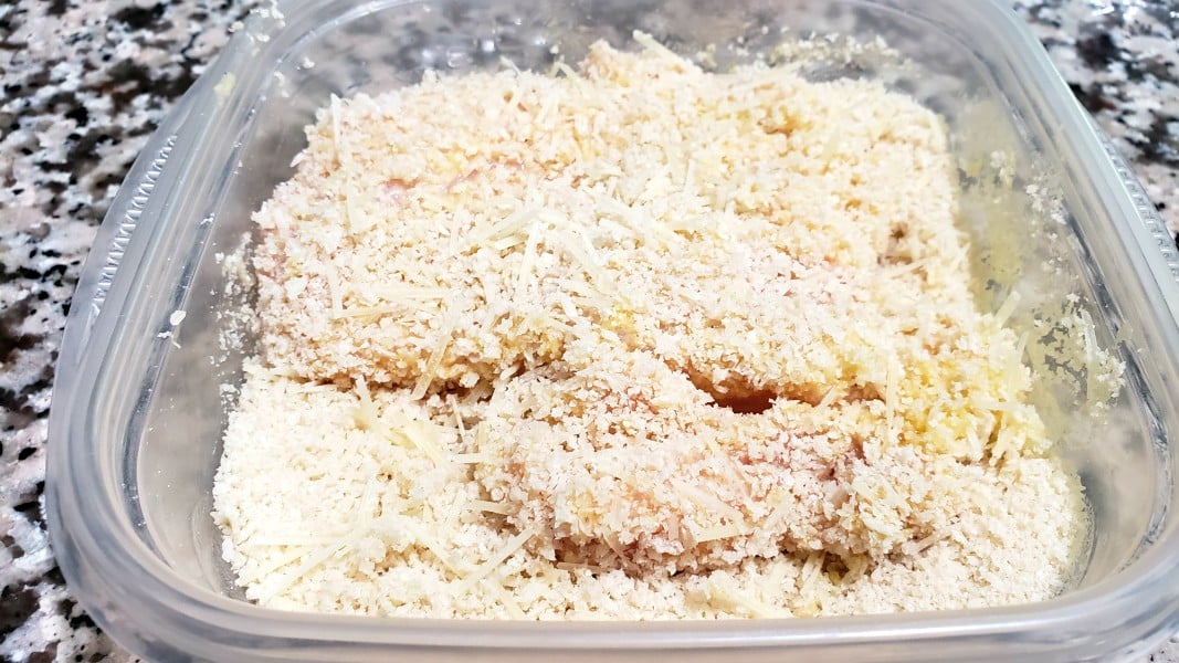 a piece of flour and egg coated chicken dipped in panko and parmesan mixture