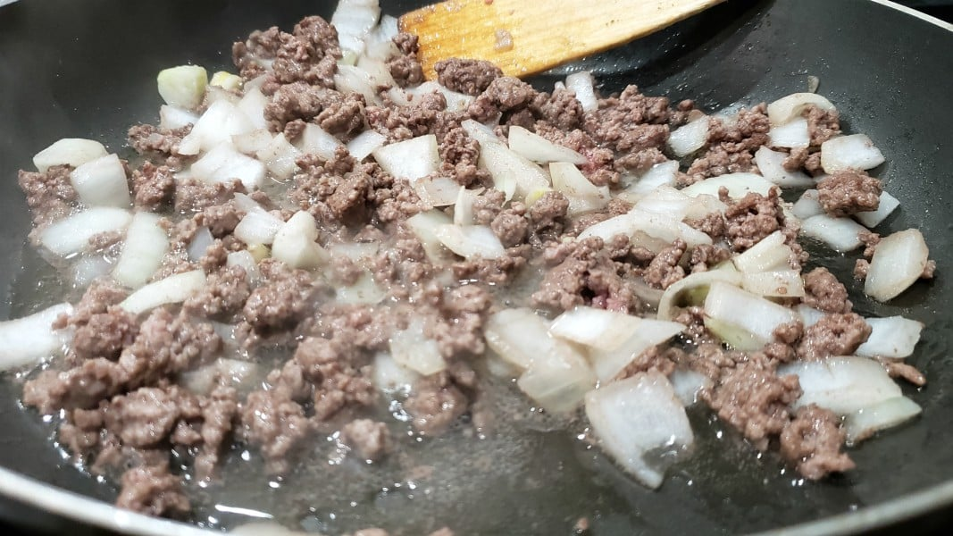 ground beef and onions cooking in a pan