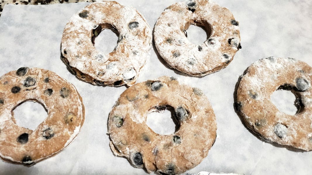 five uncooked donuts on parchment paper