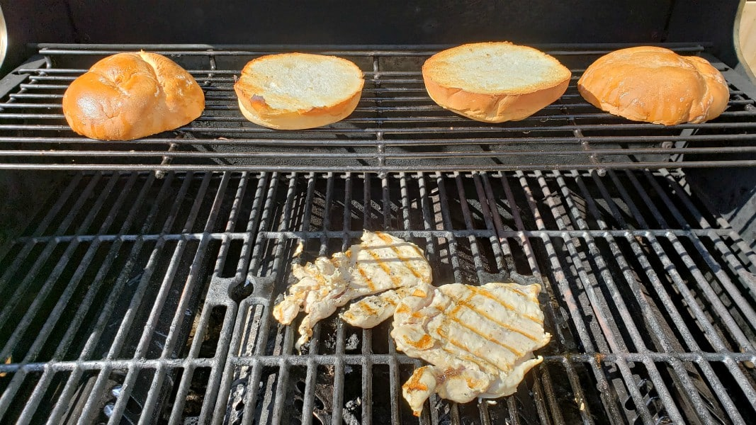 two pieces of chicken grilling and two toasted sandwich buns on the warmer rack