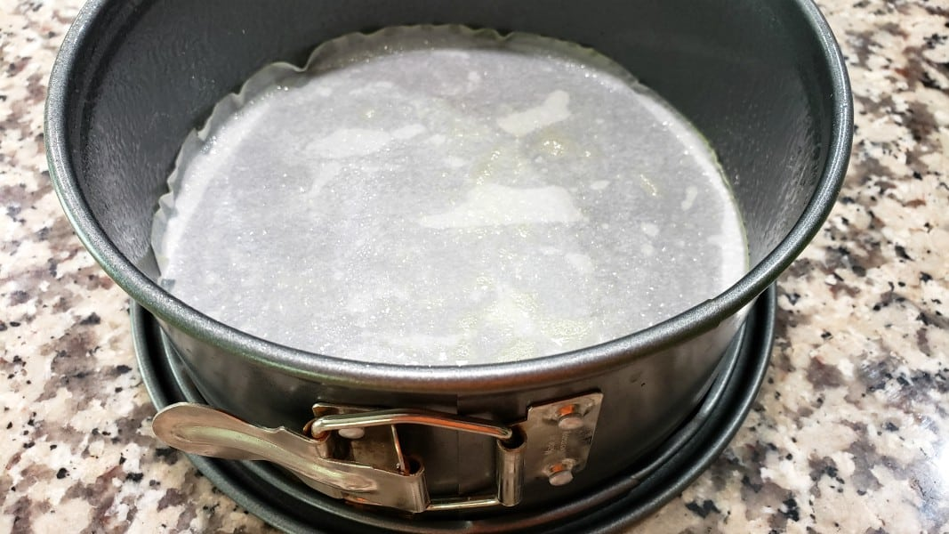 leak proof springform pan with parchment paper and coated in non-stick spray
