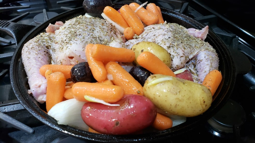 unbaked cornish hens and veggies in a cast iron skillet