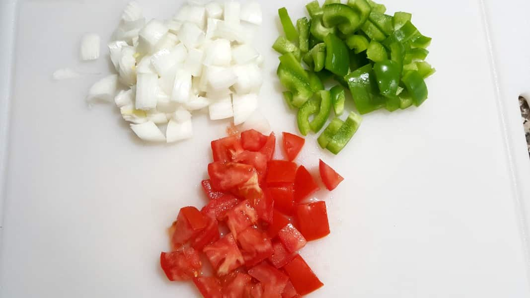 diced onions, green peppers, and tomatoes on a cutting board