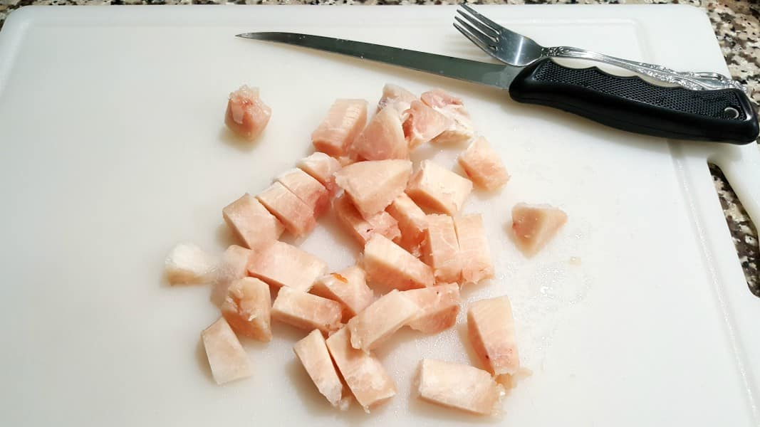 diced chicken on a cutting board with a filet knife and a fork