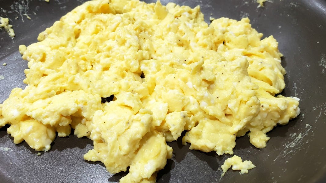 scrambled eggs cooking in a frying pan