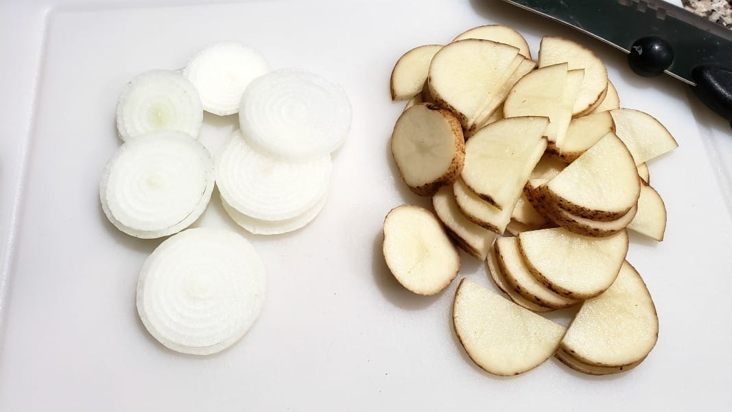 onion sliced and potato sliced on a cutting board