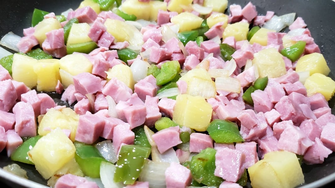 ham, pineapple, green pepper, and onion cooking in a pan