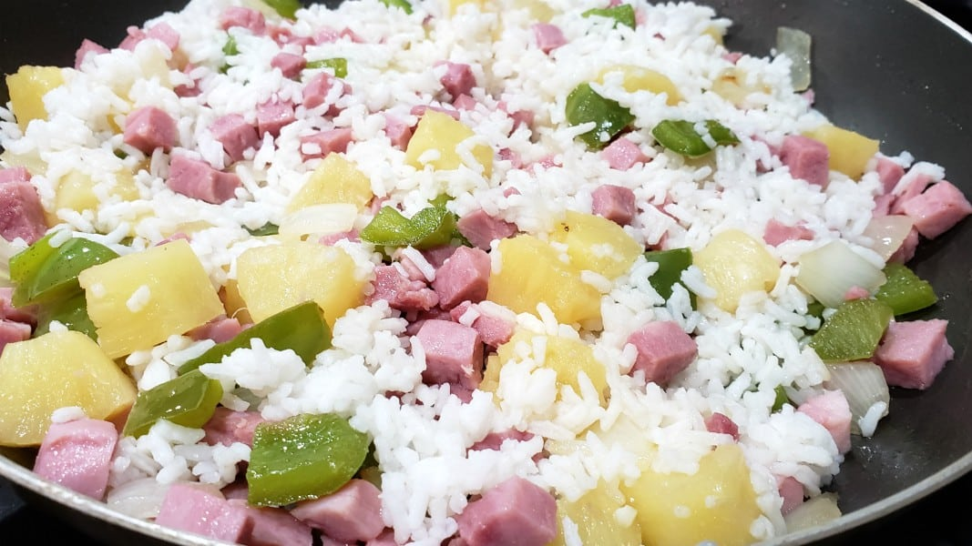 ham, pineapple, green pepper, rice and onion cooking in a pan