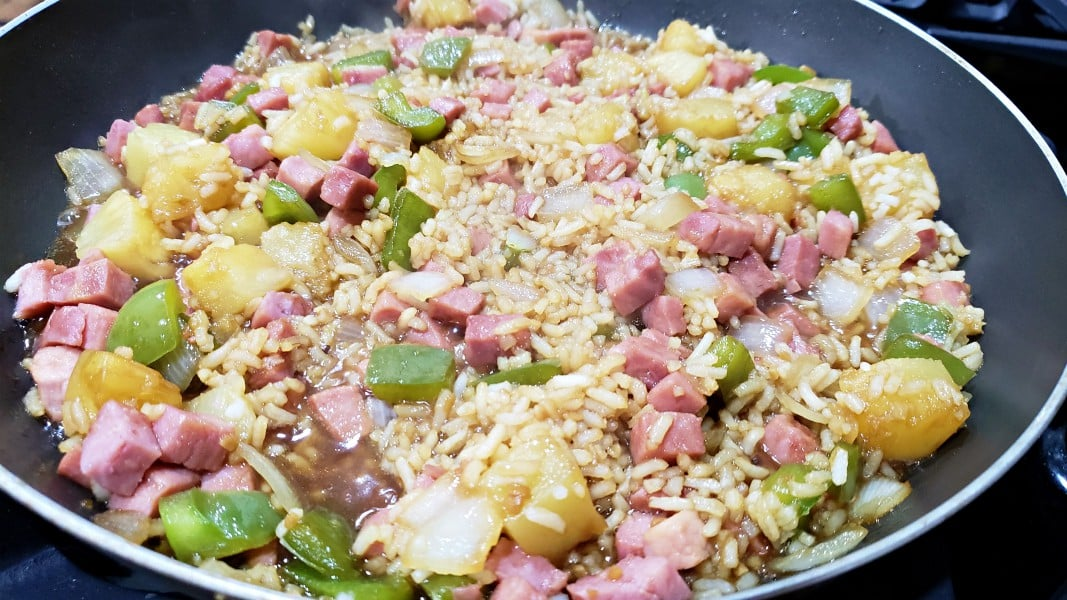 ham and pineapple fried rice cooking in a pan