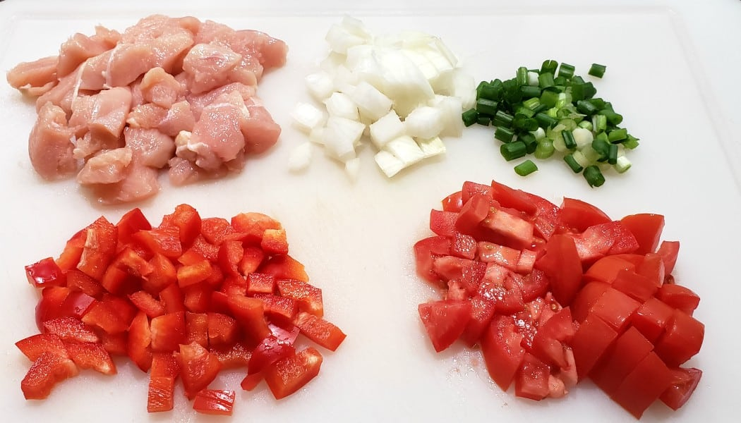 diced chicken, onion, green onion, red bell pepper, and roma tomato on a cutting board