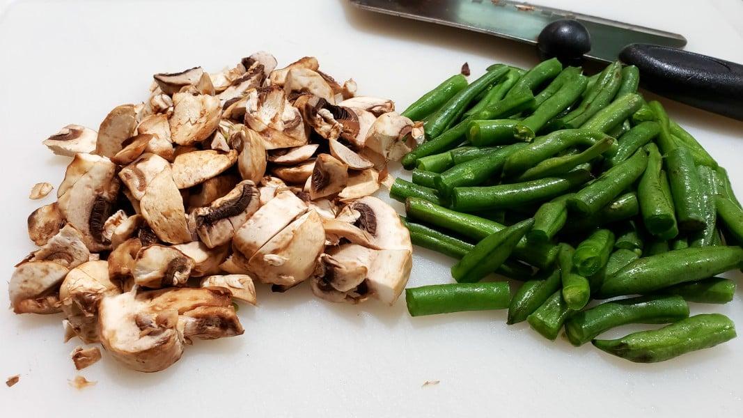 chopped mushrooms and cut green beans on a cutting board