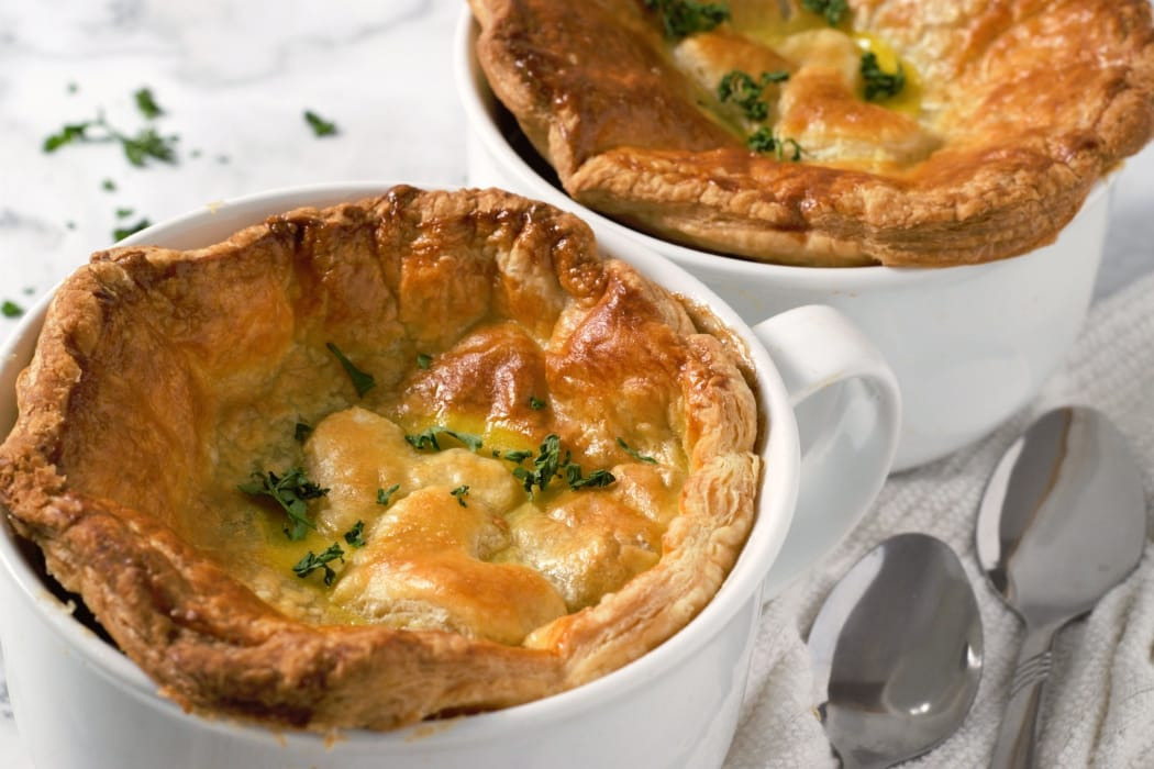 two individual beef pot pies with two spoons