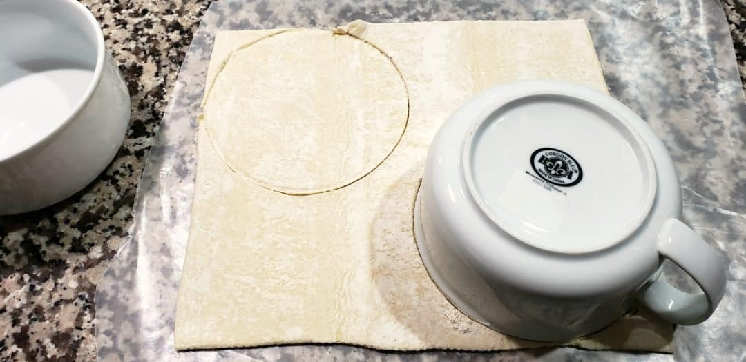 puff pastry sheet with bowl on top, circles traced to cut out