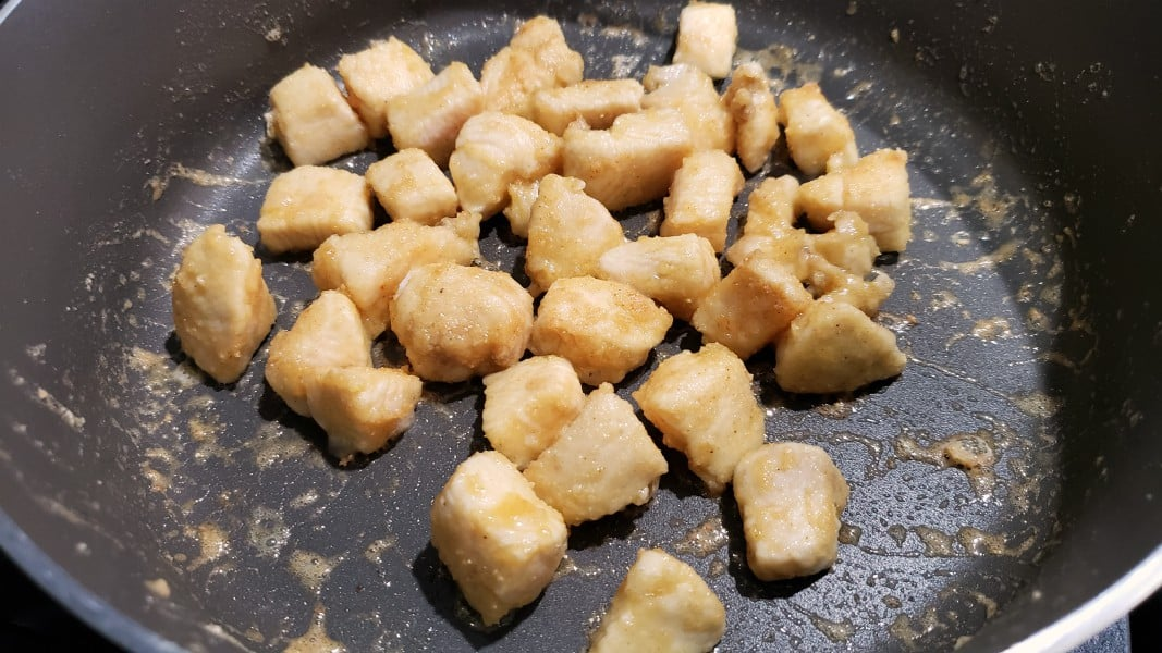 chicken coated in fry mix cooking in a pan