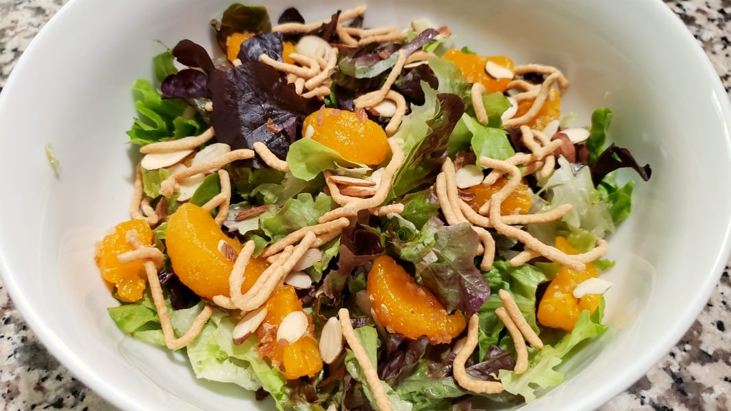 lettuce, almonds, chow mein noodles and oranges in a bowl