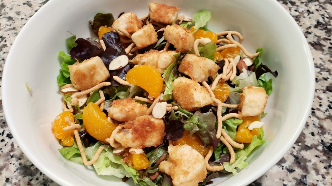 lettuce, almonds, chow mein noodles, chicken and oranges in a bowl