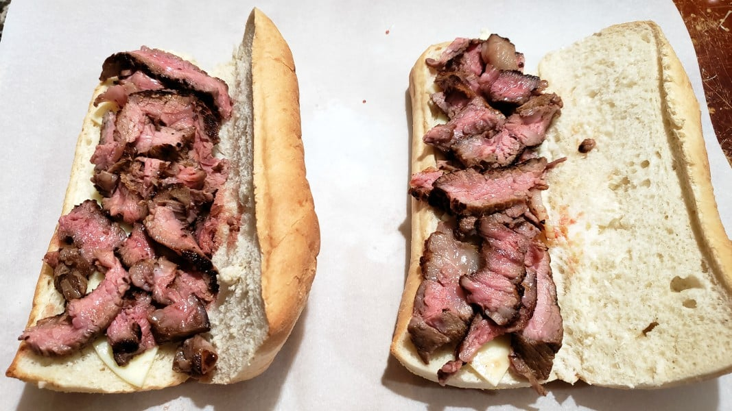 sub bun topped with provolone cheese and ribeye slices