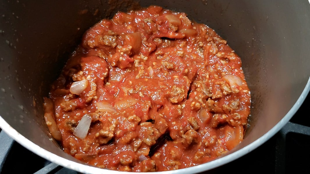 garlic, tomato sauce, tomato paste, and water added to ground beef in sauce pan
