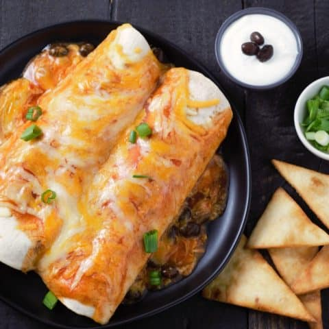 Chicken and Black Bean Enchiladas with sour cream and green onion