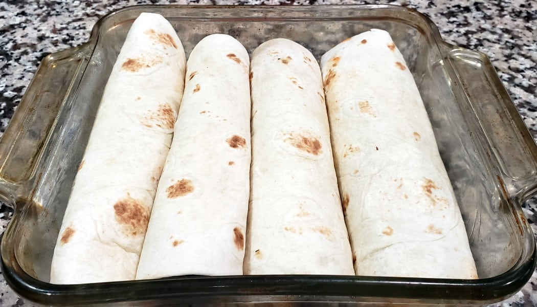 four enchiladas rolled up in a baking dish