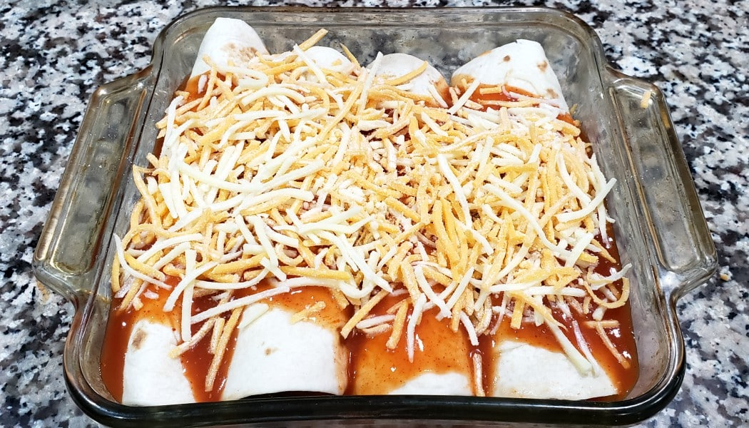 4 enchiladas topped with sauce and cheese in a baking dish