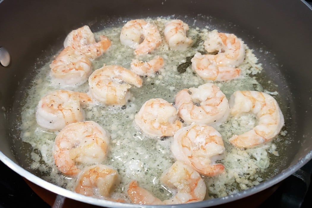 shrimp, garlic, salt, and pepper frying in a pan