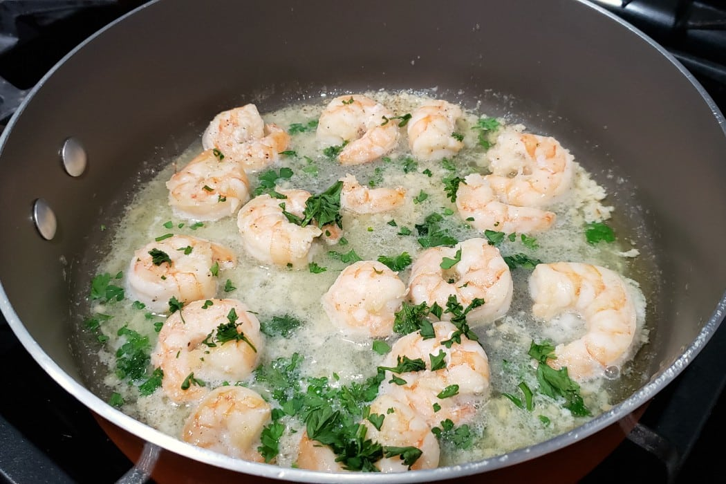 shrimp scampi frying in a pan with fresh parsley