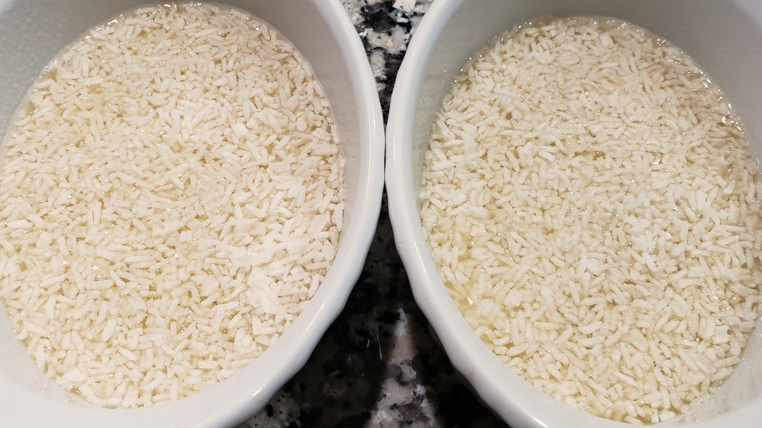 uncooked rice and chicken broth in two baking dishes