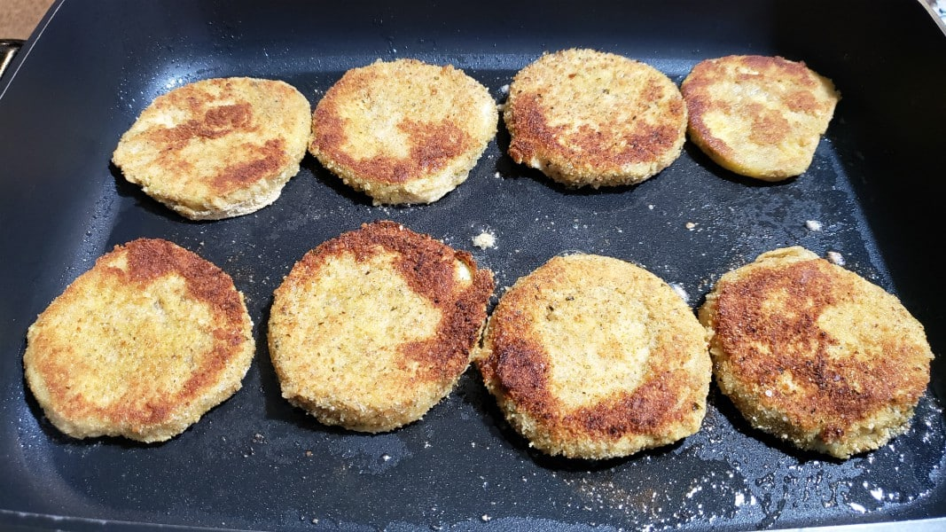 8 breaded eggplant slices frying in a skillet