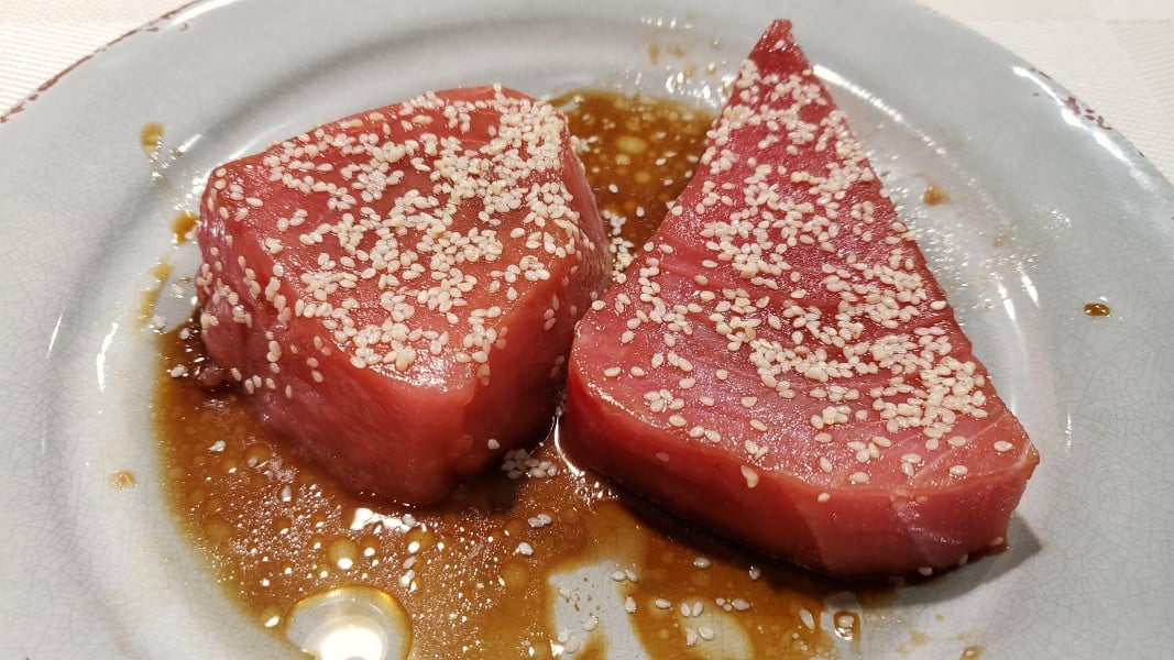 two raw tuna steaks coated in sesame seeds