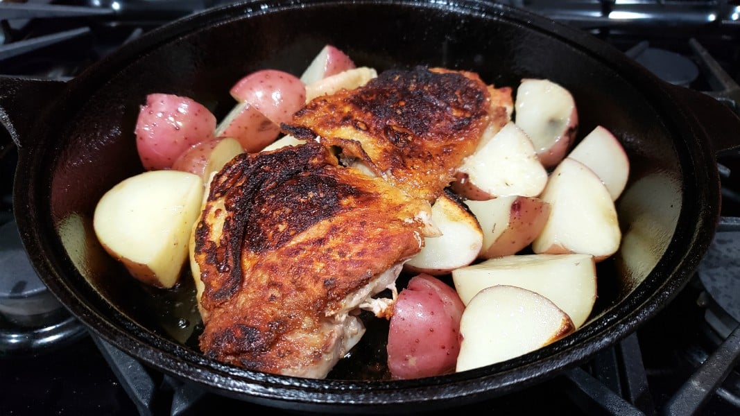 golden brown chicken thighs and potatoes in a cast iron skillet