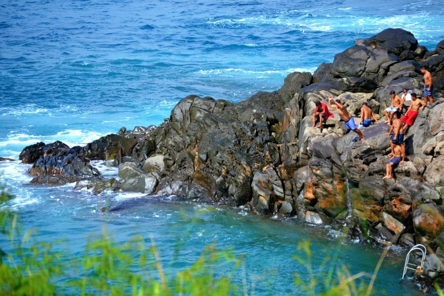 local cliff divers up high on a cliff jumping into the ocean