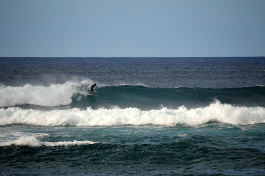 a surfer riding a wave at Ho'okipa beach park