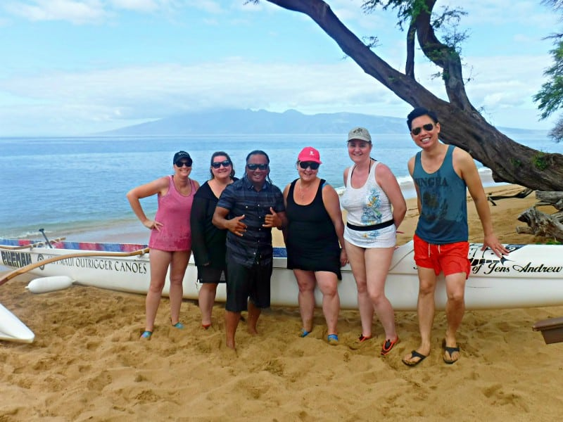 4 women and two men posing near an outrigger canoe on the beach