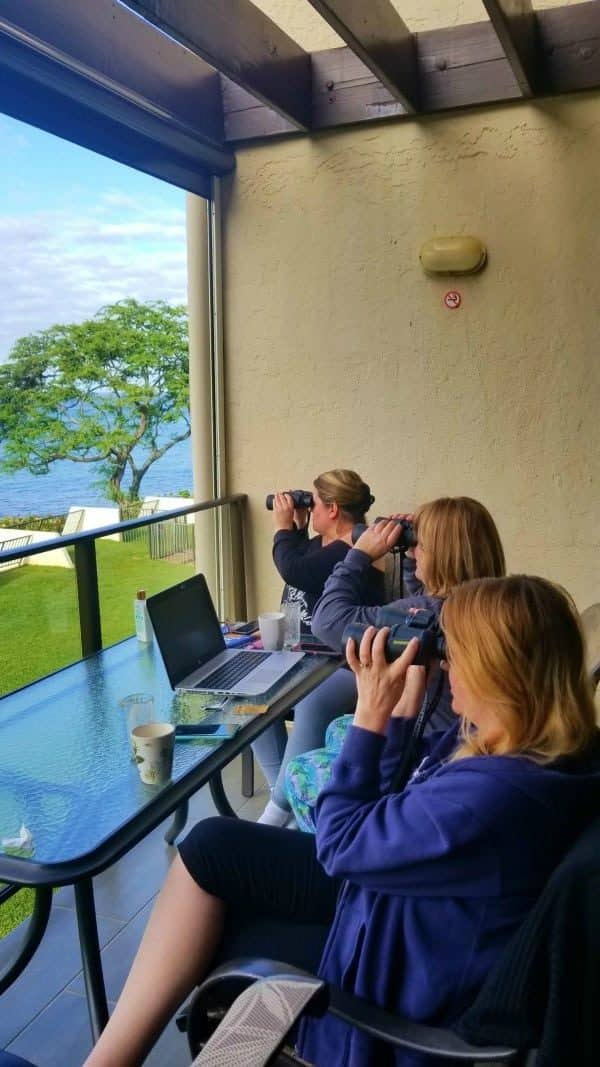 3 women looking at the ocean through binoculars