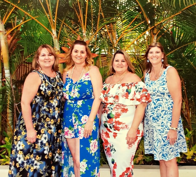 4 women dressed in Hawaiian print dresses
