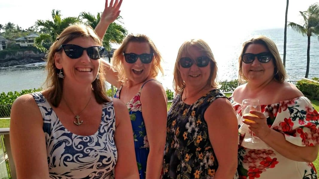 4 women in dresses with sun glasses on in front of an ocean view